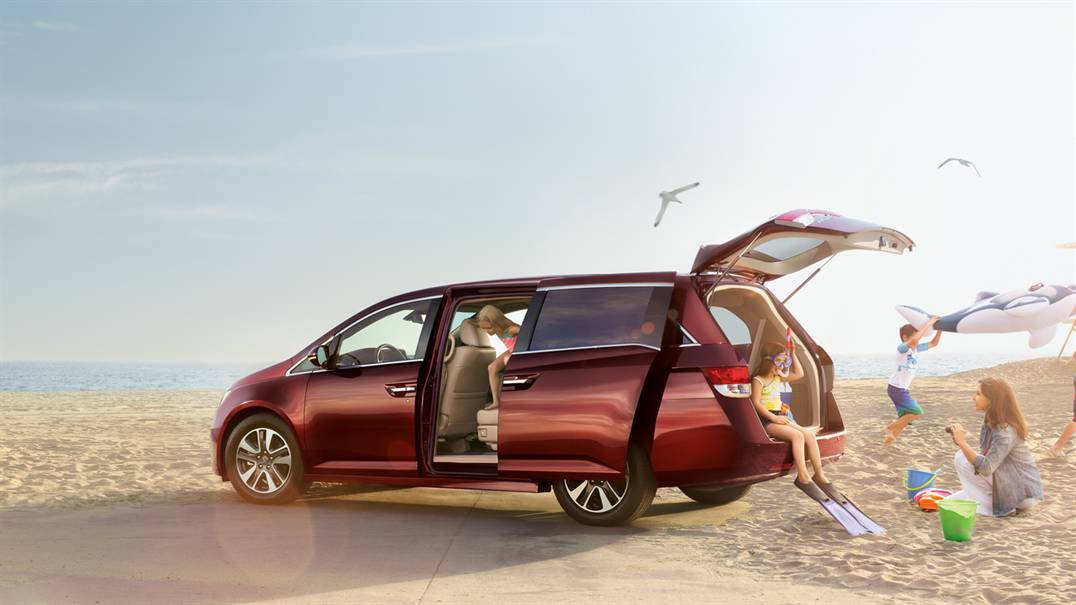 Family sitting on the beach with tailgate open on 2017 Honda Odyssey