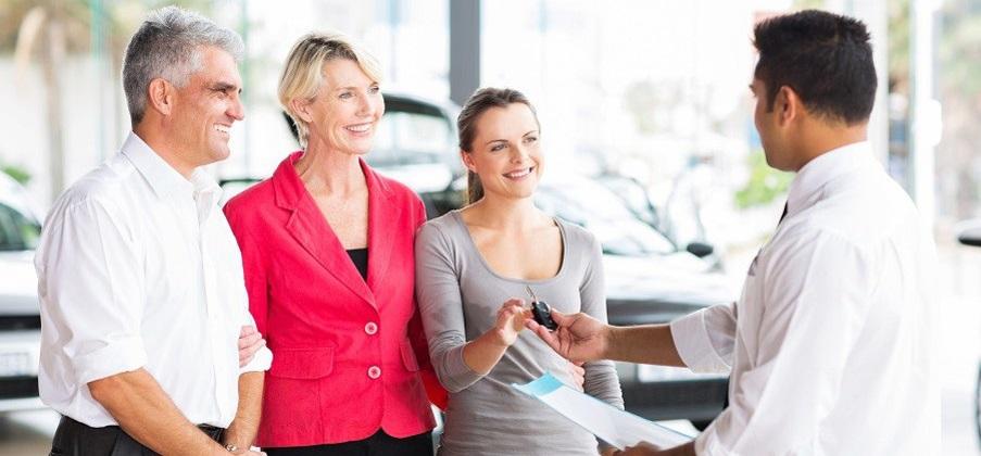 friendly salesman handing car key to customer in showroom