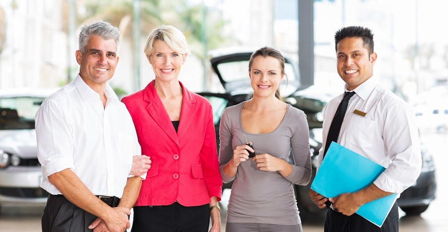 family of three standing with salesman at vehicle dealership after buying a new car
