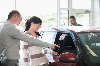 Car salesman pointing out features to customer